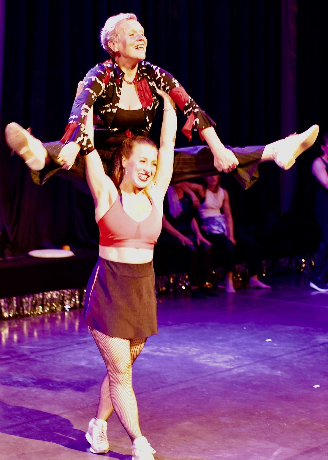 Ein Frau hebt eine andere Frau für eine Tanzeinlage in die Luft