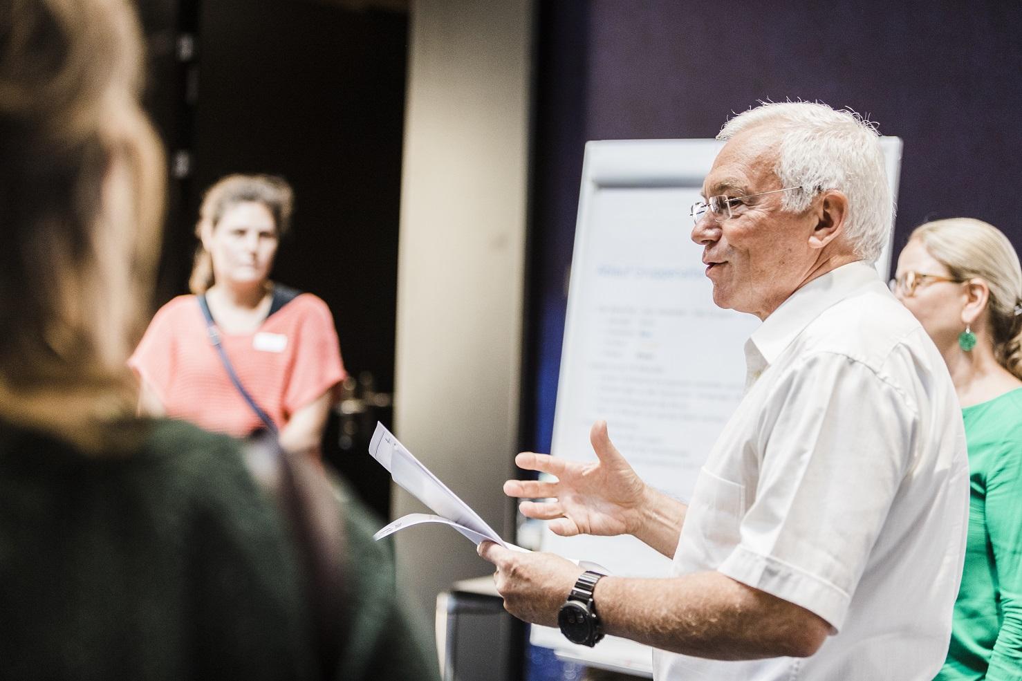 Teilnehmer übermittelt gestikulierend einen Beitrag am Workshop