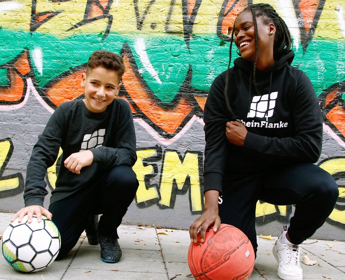 zwei Jugendliche vor einer Graffitiwand mit Bällen