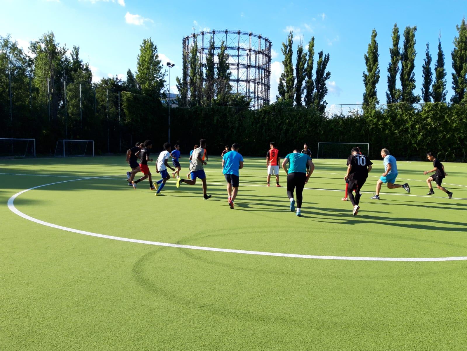 Eine Gruppe von Jugendlichen sprinten über eine grüne Wiese
