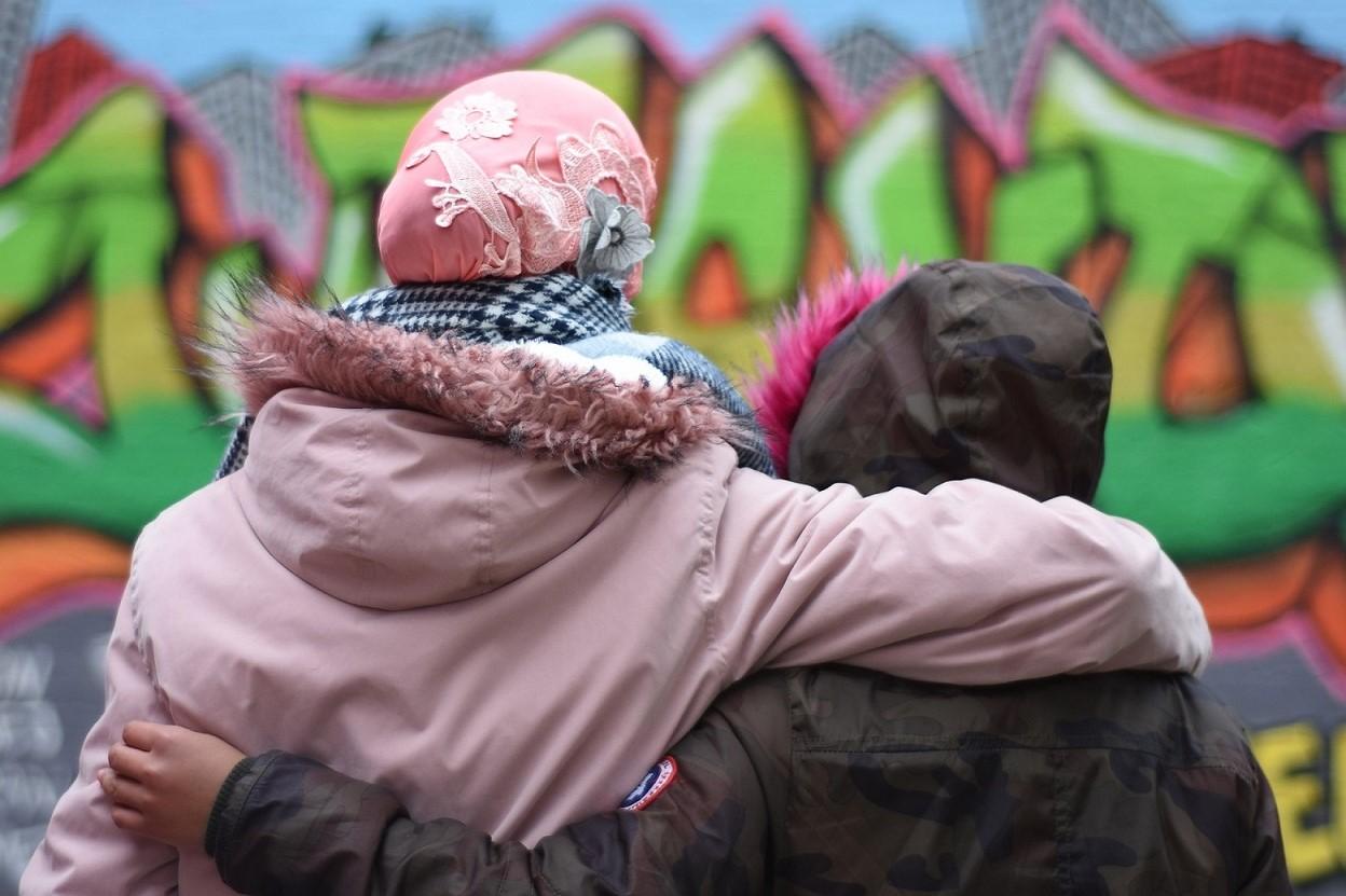 zwei Jugendliche halten sich Arm in Arm