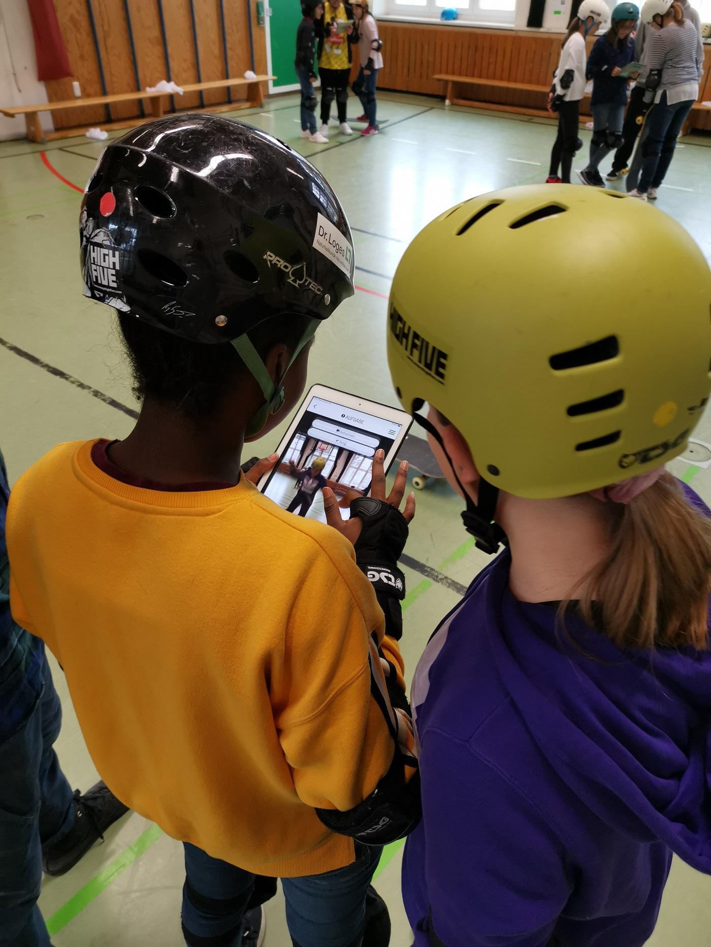 zwei Mädchen lernen den Umgang mit digital Medien im Skateboard Unterricht