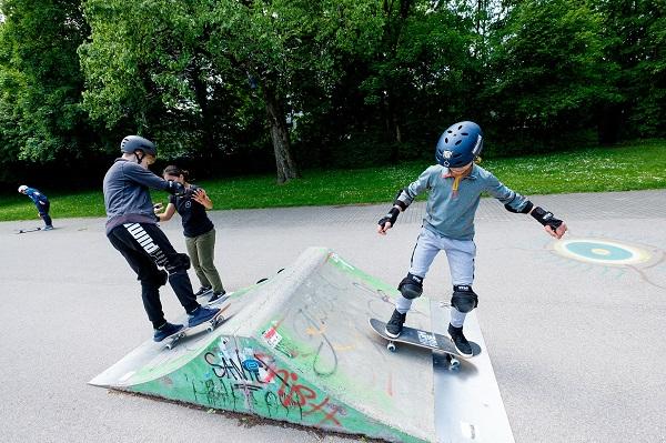 Jugendlich wagen sich mit dem Skateboard auf eine kleine Rampe