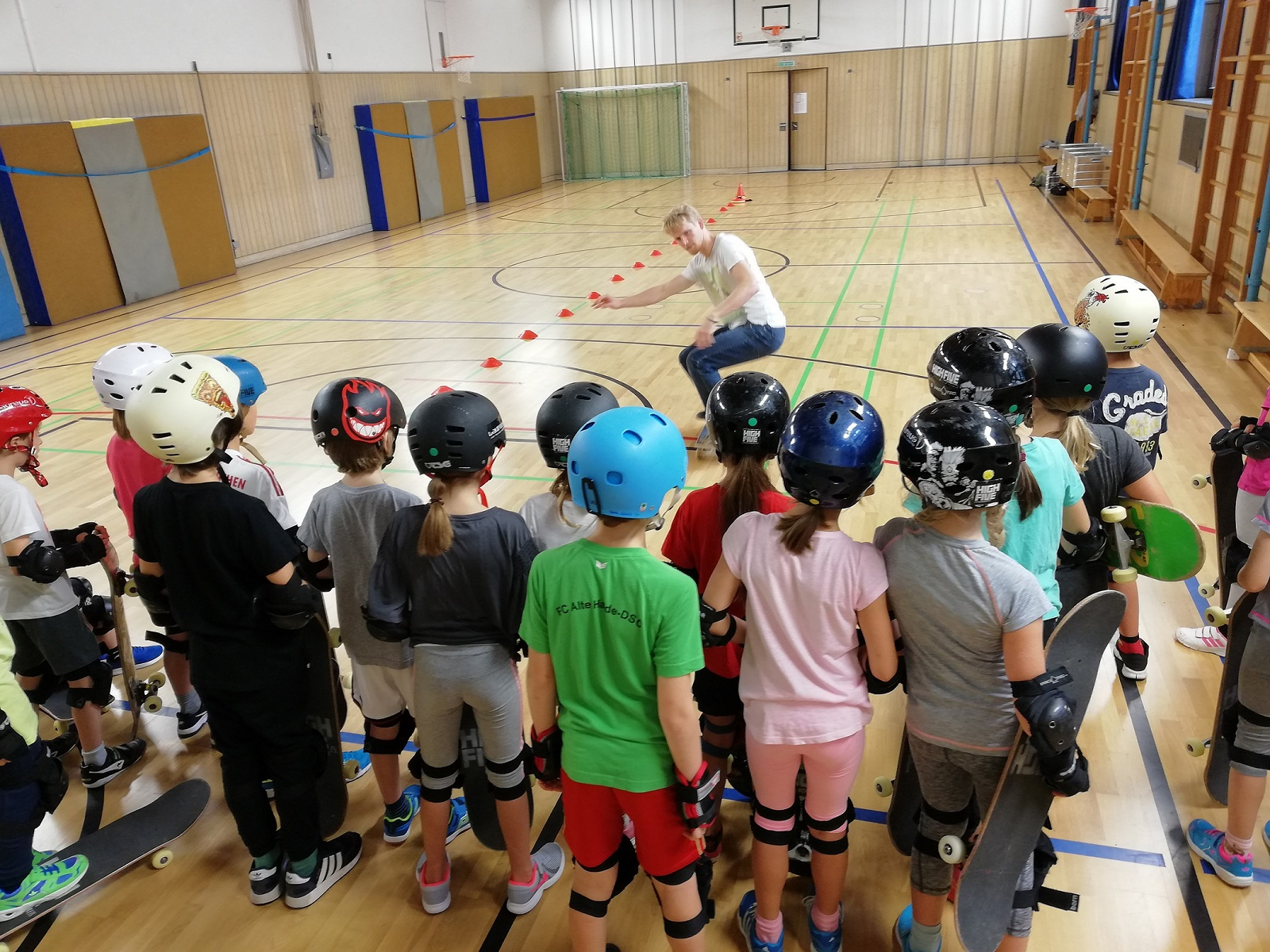 Jugendgruppe beobachtet ihren Trainer beim Vorführen der Übung